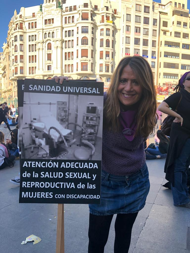 """Foto de Charo Ricart llevando una pancarta donde pone """"Atención adecuada de la salud sexual y reproductiva del las mujeres con discapacidad."""